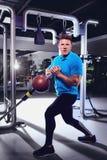 Ein sportlicher blonder Mann, der Übungen mit einem Ball in der Turnhalle tut Stockbilder
