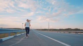 Ein sportliches Mädchen in einem weißen T-Shirt, in den hellen Turnschuhen und mit langen Haarläufen entlang einer leeren Bahn au stock video footage