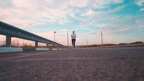 Ein sportliches Mädchen in einem weißen T-Shirt und mit dem langen Haar läuft entlang eine leere Bahn außerhalb der Stadt Von fer stock video