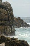 Ein Spray des Wassers gegen die Felsen Lizenzfreies Stockfoto