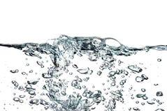 Ein Spritzen des Wassers, der Tropfen und der Blasen auf einem weißen Hintergrund Lizenzfreies Stockfoto