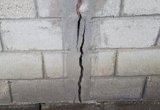 Ein Sprung in der Betonmauer Die Zerstörung der Wand von den grauen Blöcken Stockbilder