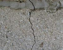 Ein Sprung in der Betonmauer Die Zerstörung der Wand von den grauen Blöcken Stockfoto