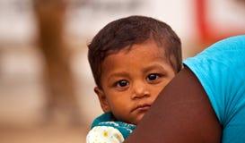 Ein sri lankan Kleinkind, das über seinen Müttern schaut, bewaffnen Lizenzfreie Stockfotos
