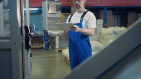 Ein Stück der arbeitenden industriellen Maschine eine männliche Arbeitskraft, die nahe ihm steht stock video