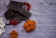 Ein Stück der Schokolade, der Moosbeere und der gestrickten Blume auf einem grauen Vorsprung Stockfoto