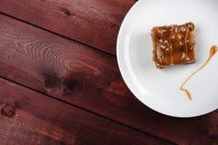 Ein Stück des Schokoladenschokoladenkuchens und Karamell sauce auf einer weißen Platte Beschneidungspfad eingeschlossen Stockfoto