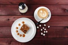 Ein Stück des Schokoladenschokoladenkuchens und Karamell sauce, eine Schale Cappuccino auf einer weißen Platte Beschneidungspfad  Stockfoto
