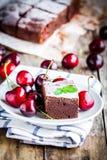 Ein Stück des selbst gemachten Schokoladenschokoladenkuchennachtischs mit einer Kirsche Stockfoto