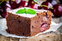 Ein Stück des selbst gemachten Schokoladenschokoladenkuchennachtischs mit einer Kirschnahaufnahme Stockfoto