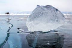 Ein Stück Eis auf der Oberfläche des blauen gefrorenen Baikalsees mit Auto am Hintergrund Stockfoto