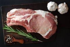 Ein Stück Fleisch von einer Schweinefleischmittelrippe vom rind mit Rosmarin, Knoblauch und Pfeffer Lizenzfreie Stockbilder
