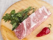 Ein Stück frisches gemarmortes Rindfleisch, Paprikapfeffer, Petersilie, Rippen liegen auf einem hölzernen Behälter Lizenzfreie Stockfotografie
