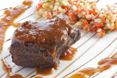 Ein Stück gebratenes Fleisch auf dem Grill mit Soße Lizenzfreie Stockfotos