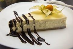 Ein Stück Käsekuchen auf einer weißen Platte mit Schokolade Lizenzfreie Stockfotografie