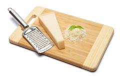 Ein Stück Parmesankäse und geriebener Käse auf Schneidebrettweißhintergrund Lizenzfreies Stockbild