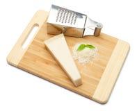 Ein Stück Parmesankäse und geriebener Käse auf Schneidebrettweißhintergrund Stockfotos