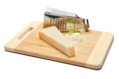 Ein Stück Parmesankäse und geriebener Käse auf Schneidebrettweißhintergrund Lizenzfreie Stockfotos