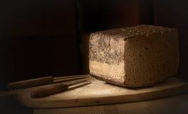 Ein Stück rustikales Brot und zwei Messer Stockfotografie