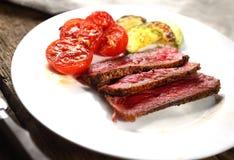 Ein Stück Steak mit Tomate und grüner Soße auf einem hölzernen Hintergrund Stockbilder
