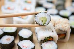 Ein Stück Sushi mit Essstäbchen aufheben Stockbild