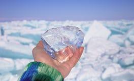 Ein Stück transparentes Kristalleis in der Hand gegen gefrorenen See am sonnigen Tag Stockfotografie