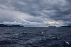 Ein stürmisches Meer mit dunklen Wolken und Inseln Lizenzfreies Stockfoto
