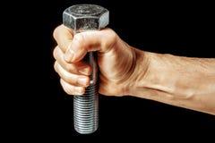 Ein Stahlbolzen in der männlichen Hand Lizenzfreie Stockfotos