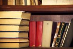 Ein Stapel alte Bücher auf dem Hintergrund von Bücherregalen Stockfotografie