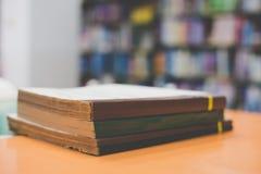 Ein Stapel alte Bücher auf Tabelle mit Unschärfebuch in der Bibliothek Lizenzfreies Stockbild