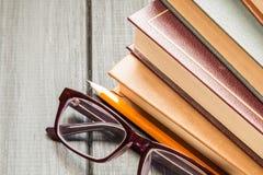 Ein Stapel alte Bücher und Gläser für das Ablesen Stockfotografie