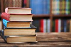 Ein Stapel alte Papierbücher auf einem Holztisch Bücherregale im Hintergrund Unscharfer Hintergrund Stockbild