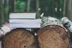 Ein Stapel Bücher, die auf gefällten Bäumen, Abwehrbäume - gelesenes ebook liegen lizenzfreies stockbild