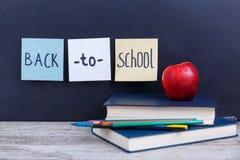 Ein Stapel Bücher, farbige Bleistifte und ein roter Apfel, auf einem dunklen Hintergrund mit der Aufschrift zurück zu Schule Stockbilder