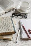Ein Stapel Bücher, Notizbuch und Gläser, Kaffeetasse auf weißem Holztisch Stockbild