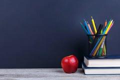 Ein Stapel Bücher, roter Apfel und bunte Bleistifte in einem Fall, auf einem dunklen Hintergrund mit einem Platz für Aufschrift Stockfotos