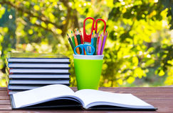 Ein Stapel Bücher und Glas mit farbigen Bleistiften Ein Satz Briefpapiereinzelteile im grünen Glas Ein offenes Buch auf einem Hol Lizenzfreie Stockfotografie