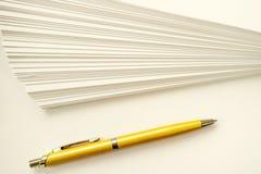 Ein Stapel Blätter des Weißbuch- und Ballpunktgoldstiftes Lizenzfreie Stockfotos