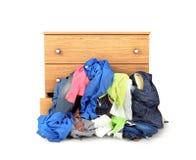 Ein Stapel der Kleidung, die aus dem Aufbereiter heraus fällt Stockfotografie