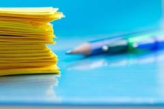 Ein Stapel des gelben Papiers und des Bleistifts auf einer blauen Tabellennahaufnahme lizenzfreie stockfotos