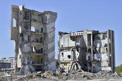 Ein Stapel des konkreten Rückstands auf dem Hintergrund eines großen zerstörten Gebäudes Hintergrund Das Konzept der Konsequenzen stockbilder