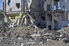 Ein Stapel des konkreten Rückstands auf dem Hintergrund eines großen zerstörten Gebäudes Hintergrund Das Konzept der Konsequenzen lizenzfreie stockbilder