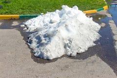 Ein Stapel des schmutzigen Schnees liegend auf der Straße Stockbilder