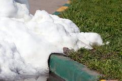 Ein Stapel des schmutzigen Schnees liegend auf der Straße Stockfoto