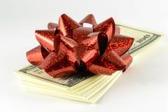 Ein Stapel Dollar und ein rotes Geschenk beugen Stockbilder