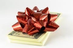 Ein Stapel Dollar und ein rotes Geschenk beugen Stockbild