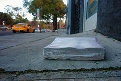 Ein Stapel eingewickelte oben Zeitschriften, die vor einer Haustür legen lizenzfreies stockfoto