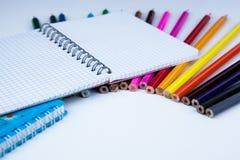 Ein Stapel farbige Bleistifte mit Notizbuch Stockfoto