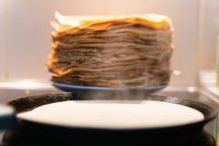 Ein Stapel gebrauchsfertige gebratene Pfannkuchen Pfannkuchen werden auf einer schwarzen Bratpfanne gebraten stockbild