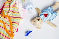 Ein Stapel Kleidung der Kinder, Spielwaren, Friedensstifter Lizenzfreies Stockbild